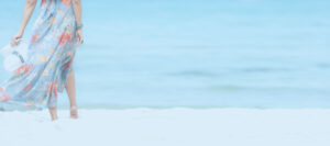 Summer Holiday. Lifestyle woman chill holding big white hat and wearing dress fashion summer trips standing chill on the sandy ocean beach. Happy people enjoy and relax vacation. Lifestyle and Travel Concept.  copy space and banner for text